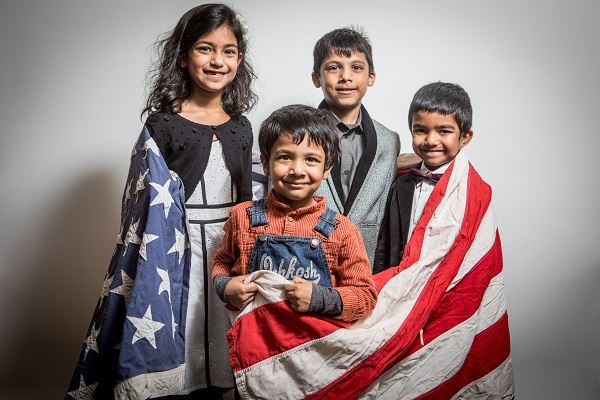 Children wrapped in an American flag at the 2017 Naturalization Ceremony