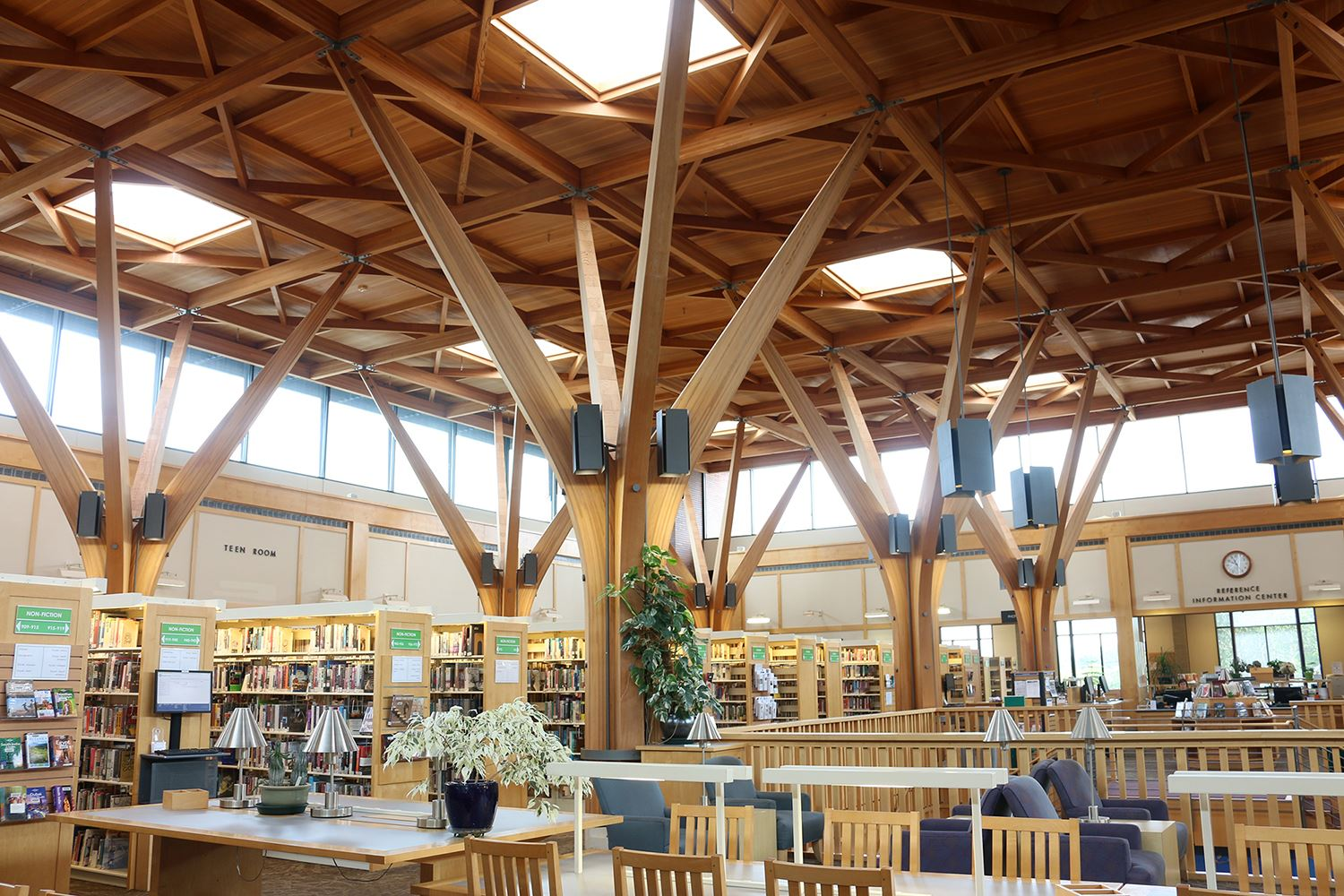 Photo of the inside of a library building with many windows and a wood ceiling and pillars.
