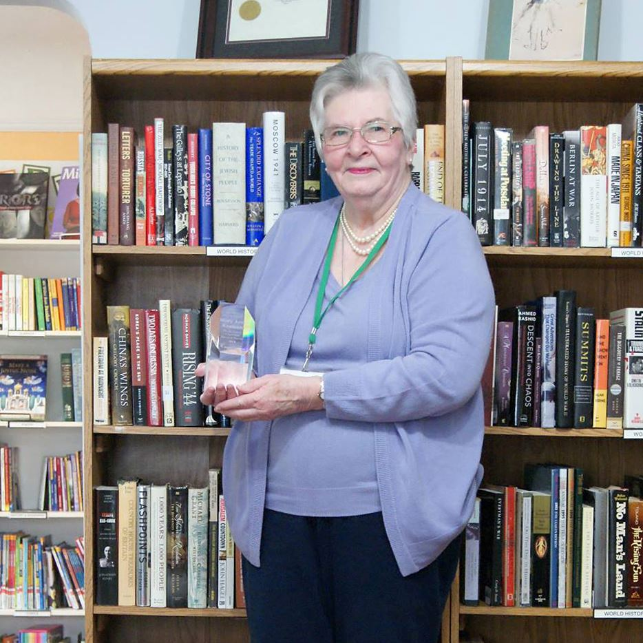 Photo of an older woman holding an award and standing in front of a bookcase.