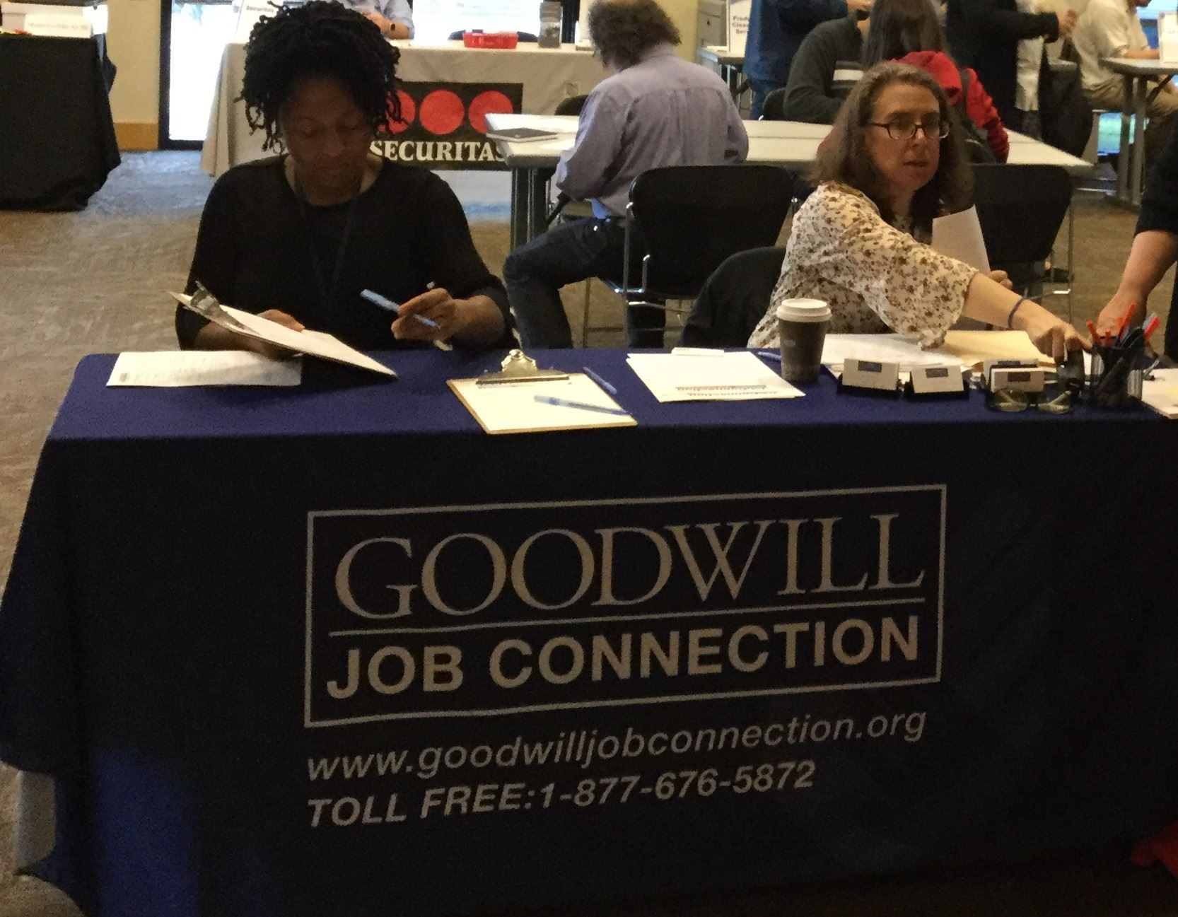 Two people sitting at a table with a banner that says Goodwill Job Connection Job Fair